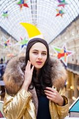 Beautiful brunette woman in golden fur coat