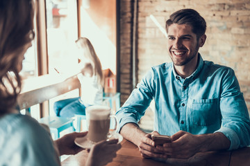 Happy man with phone sits in coffee shop with girl.