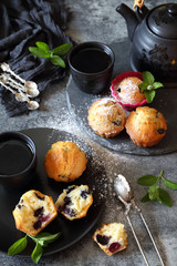 Blueberry muffins, powdered sugar dressing and teapot