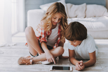 Little beautiful girl and boy are browsing Internet on tablet of house.