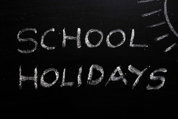 School holidays text and sun drawing on chalkboard