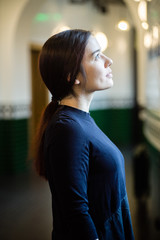 Indoor portrait of young beautiful model of mixed race dressed in black dress standing at the corridor with green tiles
