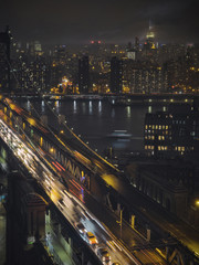 Light trails bridge over river in illuminated city at night