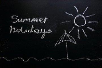 Sun and sunshade drawing on chalkboard, summer holidays concept
