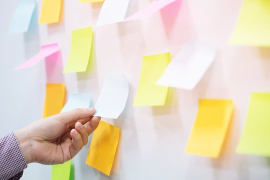 close up hand people business man post it notes in the wall at meeting room. Sticky note paper reminder schedule board. Colorful variety copy empty space. soft focus.