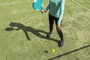 Low section of woman playing paddle tennis on court during sunny day