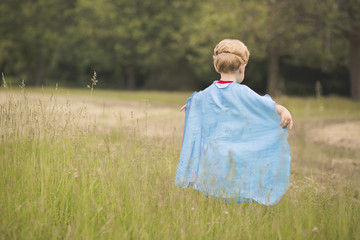 Rear view of boy wearing blue cape while playing on grassy field at public park