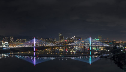 Reflection of illuminated city and bridge in river against sky at night