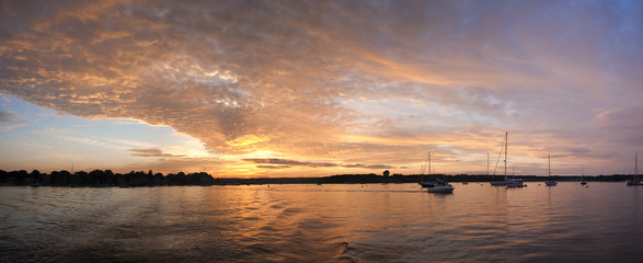 Panoramic view of boats in lake against dramatic sky during sunset