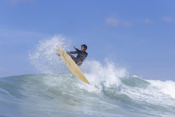 Man surfing on sea against blue sky