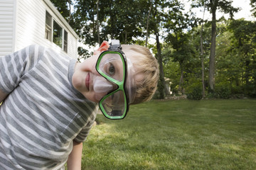 Portrait of playful boy wearing swimming goggles on grassy field at backyard