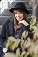 Portrait of smiling woman wearing hat while sitting by plants