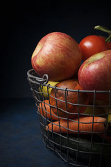 Close-up of fruits with vegetables in metal basket on table