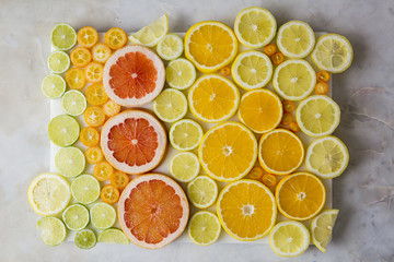 Overhead view of various citrus fruits arranged on marble table