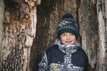 Portrait of smiling boy standing by tree trunk in forest during winter