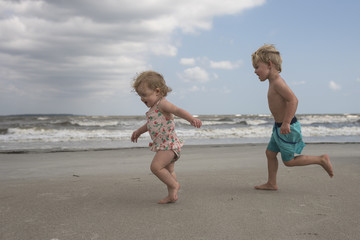 Side view of playful siblings running at beach against cloudy sky
