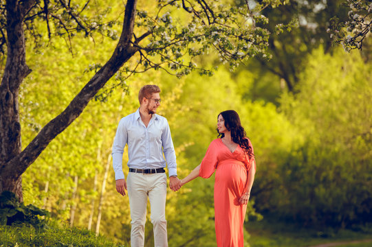 Romantic portrait of young smiling happy couple of lovely future parents during sunset on nature apple tree background in the city park. Pregnancy pregnant future mother photoshoot. Motherhood photo