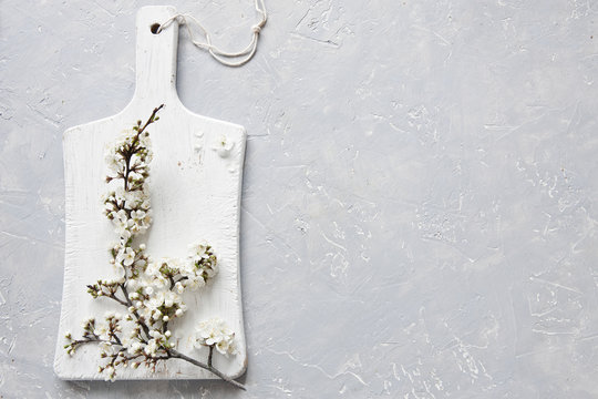 Close-up photo of beautiful white blooming flowers of cherry tree branch on white wooden cutting board on grey background