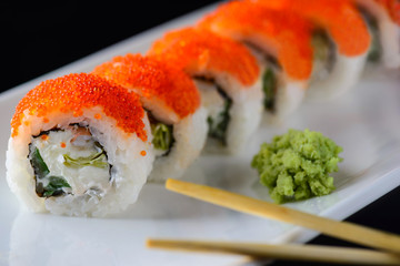 sushi rolls with red caviar on a white plate