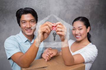 Happy couple holding house key and leaning on moving box against house outline in clouds