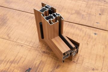 Sezione di un profilo in alluminio per finestre e porte,isolato su tavolo di legno