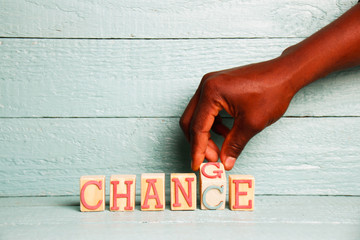 A hand flips a wooden cube with the words change into the word chance