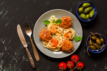 Spaghetti with meatballs in tomato sauce served in a gray plate, capers, olives, tomatoes. Black concrete background, top view.