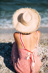 Young girl in a hat sits on the beach at sunset, happily travels and enjoys the sea views