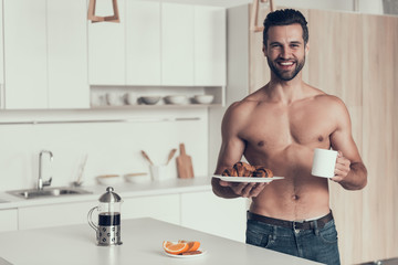 Handsome man with naked torso cooked fresh coffee and croissant.