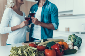 Loving couple with glasses of wine prepare breakfast together.