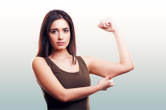 Woman pinching flabby fat arm skin
