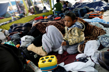 A child traveling with a caravan of migrants from Central America sits at a camp near the San Ysidro checkpoint, after U.S. border authorities allowed the first small group of women and children entry from Mexico overnight, in Tijuana