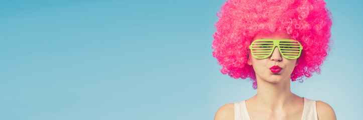 Portrait of beautiful woman in pink wig and green glasses with copy space