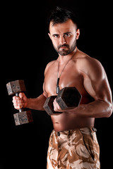 muscular man doing exercises with dumbbells.