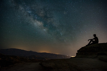 Milky way sky on the mountain with a silhouette of a person sitting on a rock