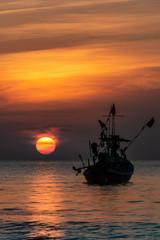 Sonnenuntergang im Meer mit Fischerboot