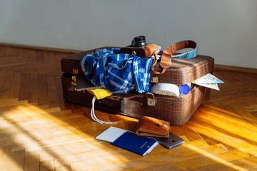 overloaded suitcase with clothes. travel concept. bag with garment. biometric passport in front