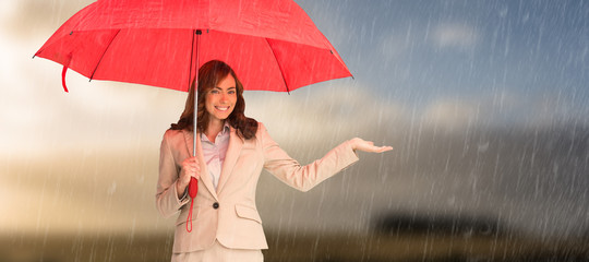 Happy businesswoman holding umbrella against cloudy sky