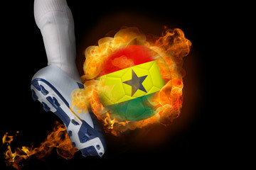 Football player kicking flaming ghana flag ball against black