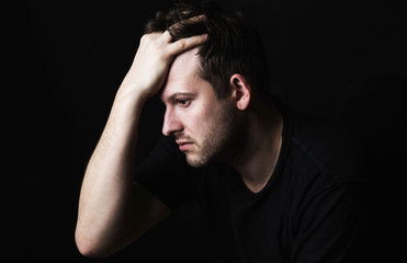 A brunette man with a bristle in a black T-shirt on a dark background holds his head in one hand. View in profile. Social problems.