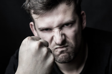 Portrait of an angry man clenching his fist on a black background. Family conflicts and violence. The concept of aggression