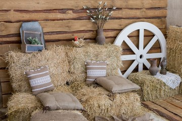 hay bales and pillows. rustic style area. jugs for milk on a haystack. straw