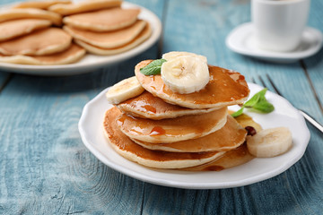 Tasty pancakes with honey and banana on table