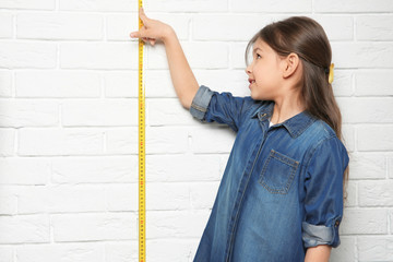 Little girl measuring her height on brick wall background