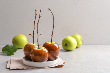 Plate with delicious green caramel apples on table