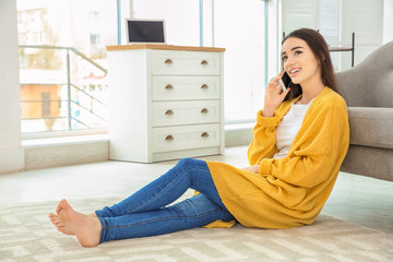 Attractive young woman talking on mobile phone near sofa