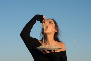 Young beautiful woman eating spaghetti, on blue sky background