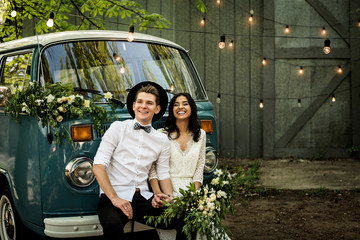 Cheerful happy young couple sit on the bumper retro-minibus.