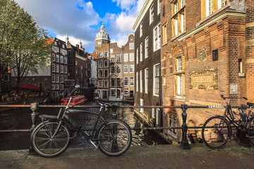 Bicycles parked on a canal bridge in Amsterdam with view of St. Nicolas Church, Netherlands