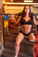 A woman performing weight lifting exercises in the Gym